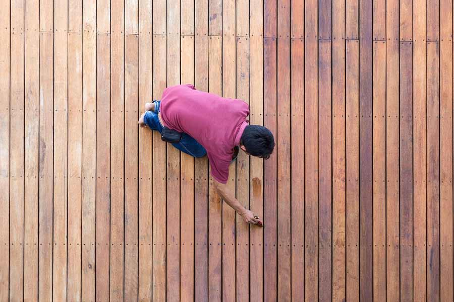 a man painting exterior deck